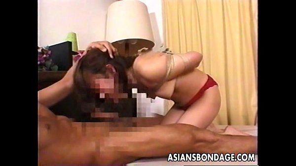 Japanese girl tied up and munching on a stiff cock